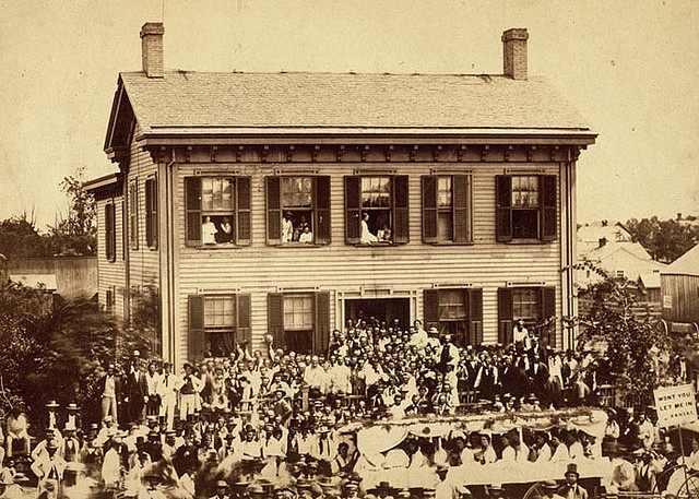 Lincoln campaign rally in Springfield, August 8, 1860. Adhering to nineteenth-century custom, Abraham Lincoln did not actively campaign for the presidency. But, he did make local  appearances. In this 1860 photograph, he is wearing a white suit, standing next to the front door of his home. Relatively unknown  outside Illinois, Lincoln benefited from having his image widely  circulated on campaign materials, like The Railsplitter.