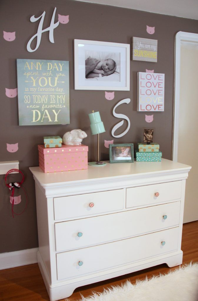 Create a gallery wall in your nursery or little girls room with art, picture frames  and accessories from HomeGoods. Inspirational art, polka dotted storage boxes, and a turquoise and gold desk lamp all from HomeGoods in pink, white and turquoise complete the dresser area. Sponsored Happy by Design Post