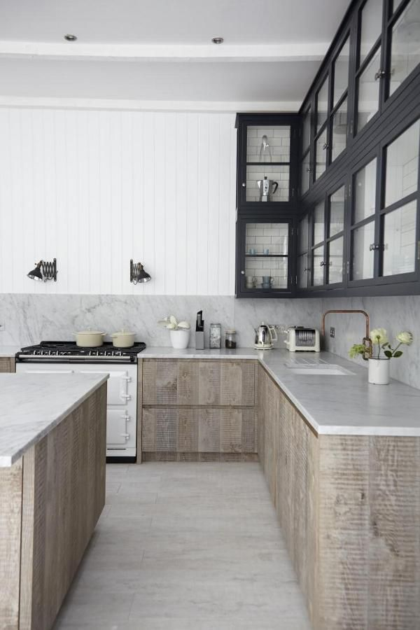 A modern kitchen with an interesting mix of materials with black steel custom upper cabinets and unfinished limed wood for the lower cabinets all mixed together with lots of white.