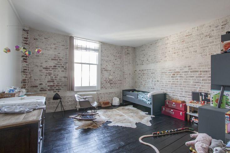 Chambre avec parquet noir et briques