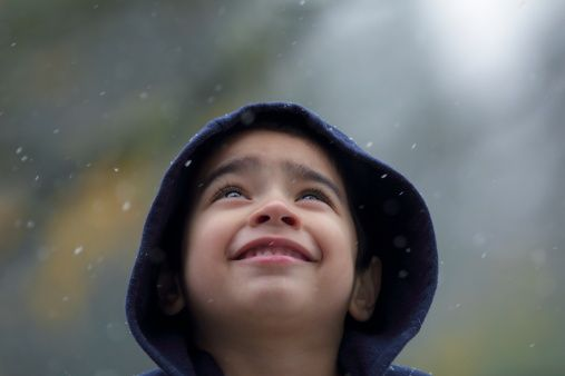 Bright eyed child looking up into a snowstorm