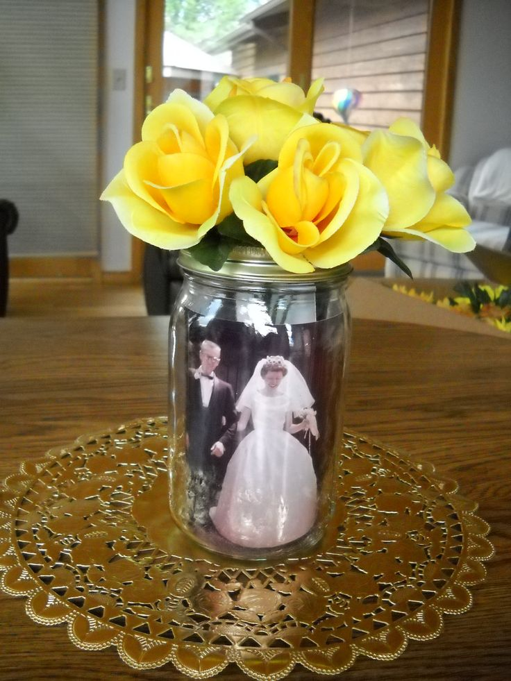 50th Wedding anniversary table centerpieces. Mason jar with photos from the past inserted inside of jar topped with silk flowers.