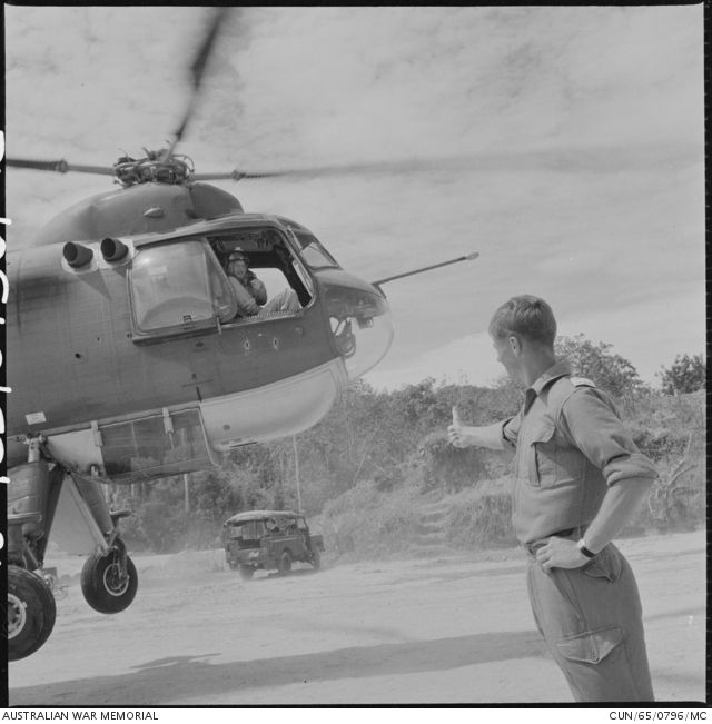 Lieutenant (Lt) Brian Hartland Mitchell, of Tamworth, NSW, 102nd Field Battery, Royal Australian Artillery (RAA), gives the all clear, thumbs up signal to an unidentified pilot of a Royal Air Force Belvedere helicopter, which has just delivered an L5 Pack Howitzer to the gun pit at a forward company base in Sarawak, North Borneo.