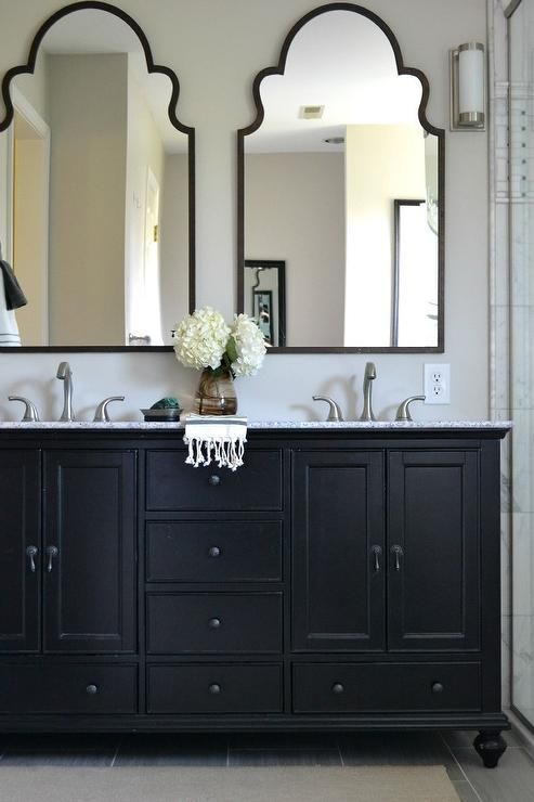 This neutral master bathroom features a beautiful black double vanity with mirrors.