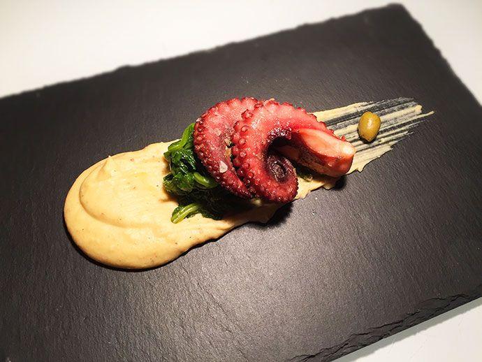Morbidezza e croccantezza insieme per questa ricetta di alta cucina gourmet di un un polpo cotto a bassa temperatura con fave e cime di rapa.