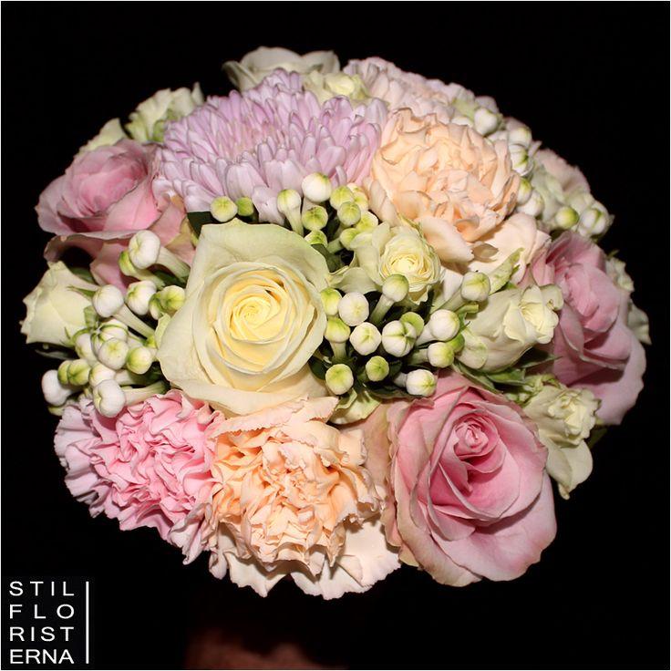 Enkel bollformad brudbukett i vita, rosa och aprikosa toner.