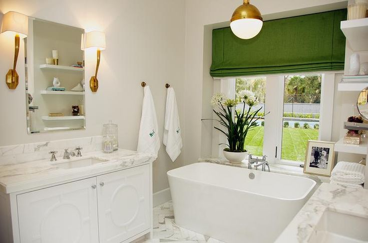 White and green bathroom features Visual Comfort Lighting Ruhlmann Single Sconces in Antique Burnished Brass flanking frameless beveled mirror over contemporary white vanity accented with geometric overlay doors topped with white and gray marble countertop over white and gray marble herringbone floor.