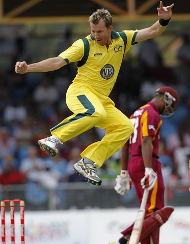 Australia's fast bowler Brett Lee jumps in the air in celebration after trapping West Indies' opener Kieran Powell, rear, LBW for a duck with his first delivery during their second one day international cricket match in Kingstown, St. Vincent, Sunday March 18, 2012. (AP Photo/Andres Leighton)