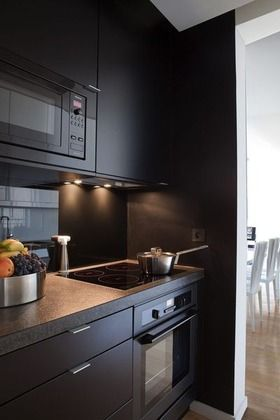 Ouverte sur la pièce principale, cette cuisine a fait l'objet d'une rénovation complète. Son agencement, sur mesure, est dû à un architecte qui a su prendre en compte les goûts, les exigences et les idées de son client, passionné de design.L'électroménager est regroupé dans le coin cuisson. Il se compose d'un réfrigérateur, d'un micro-ondes encastrable, d'un four lui aussi encastrable, d'une hotte plafond, le tout De Dietrich, et d'une plaque à induction, 4 zones de cuisson, Miele.