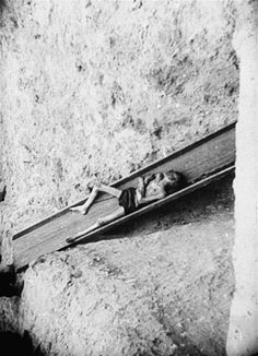 A corpse slides down a chute into a mass grave inside the Warsaw Ghetto.
