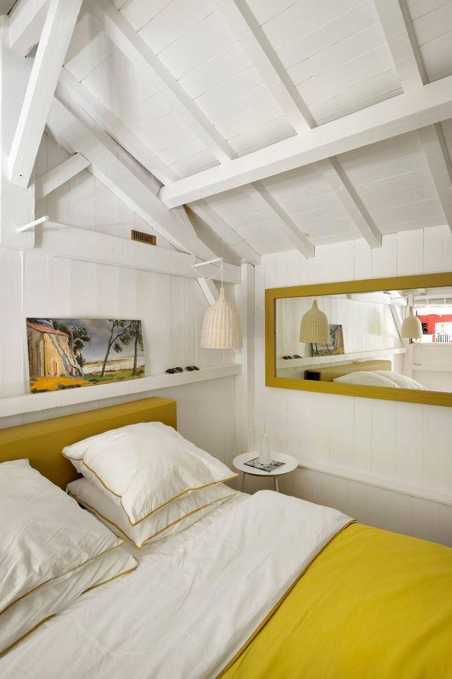 Une chambre avec poutres épurée, au linge de lit ensoleillé