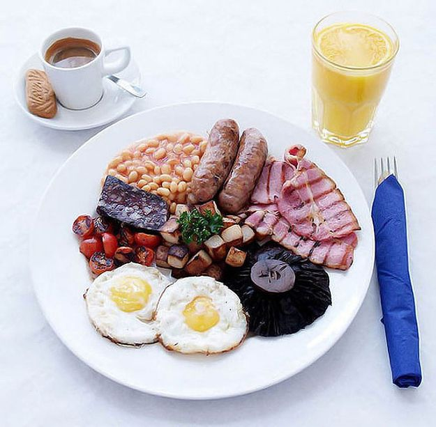 Breakfast in England, bacon, eggs, sausage, grilled tomatoes, bread, mushrooms and black pudding