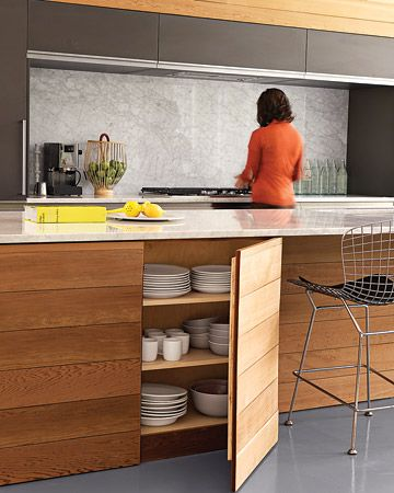 """Hidden Storage System  The streamlined kitchen of this Chicago-area home offers plenty of hidden spaces to storekitchen essentials; the island, built out of red cedar and marble, houses the owner's collection of classic HeathCeramics """"Coupe"""" tableware."""