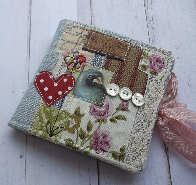 Although this is designed to be a handmade needle case, this photo does offer a great idea for a fabric mini album---the design is beautiful!!