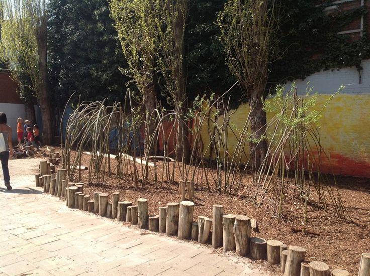 Afscheiding tussen natuurlijke zone en harde zone met (speel)boomstammetjes (De Kleine Wereldburger, Borgerhout)