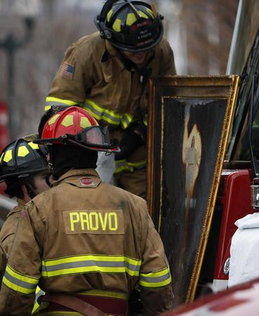 Provo Firefighters look at a painting of Christ that was burned in the fire Saturday, Dec. 18,2010. The fire burned the entire image except the image of Christ near the center. Provo City Firefighters continue their work at the historic Provo Tabernacle after the building was destroyed by fire.  (Scott G Winterton, Deseret News)