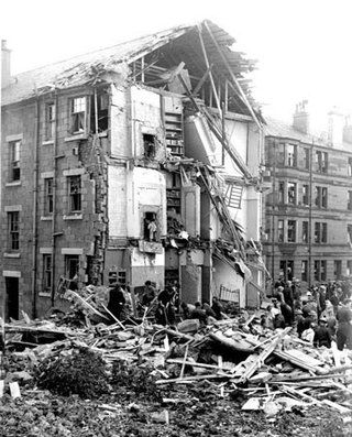Rescuers searching through the rubble of a tenement in Scotstoun following a direct hit by an HE bomb