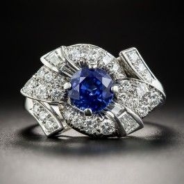 A brilliant blue sapphire glistens in the center of a striking stylized bow motif composed of bright white and sparkling round and baguette diamonds, all set in gleaming platinum. Although a stunning Art Deco design, this delightful ring probably dates from the late-1940s-1950s. .85 carat total diamond weight. 9/16 by just over 3/4 inch. Currently ring size 6.