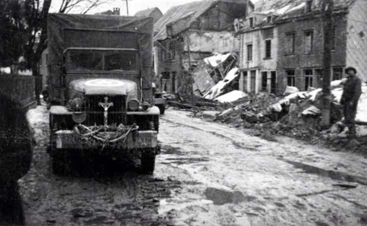 Rue devant les grands moulins 1944 - Camion Us transformé en corbillard (croix sur la calandre), Malmedy.: