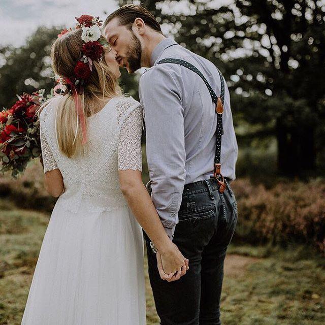 Zweiteiliges Brautkleid mit Spitzentop und Tüllrock, dazu ein großer Blumenkranz und Brautstrauß in Dunkelrot.