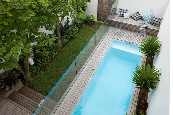 Small pool with wood deck and wood bench and glass enclosure for safety and walls for privacy.