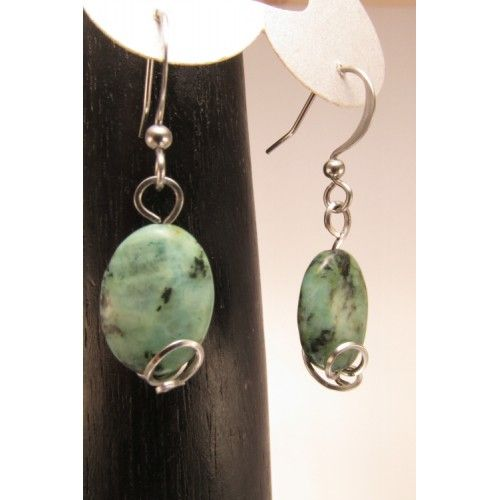 Boucles d'oreilles de forme ovale, composées de jadéites vertes. Elles sont enjolivées d'un dessin de fil d'acier inoxydable.    Bijoux artisanaux fabriqué au Québec.