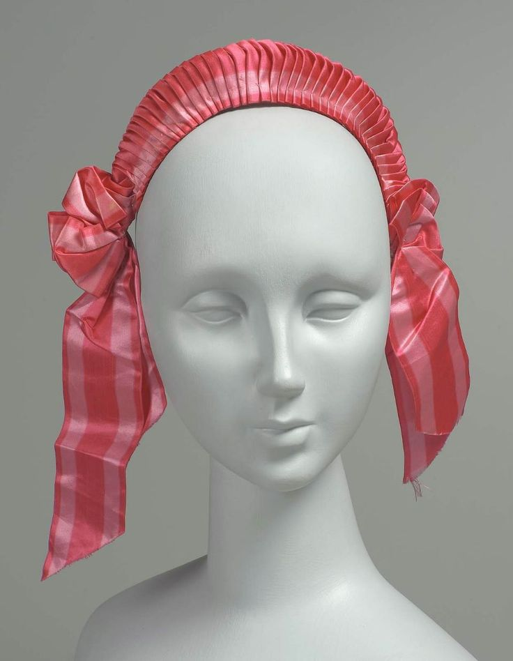wide band of striped ribbon in two shades of pink tightly pleated across top and sewn to two wires covered in white cotton threads and tape; bows with streamers at each side