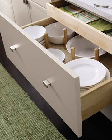 This smart drawer has a sliding shelf to keep your table linens flat and a pegged dish organizer for great space efficiency.