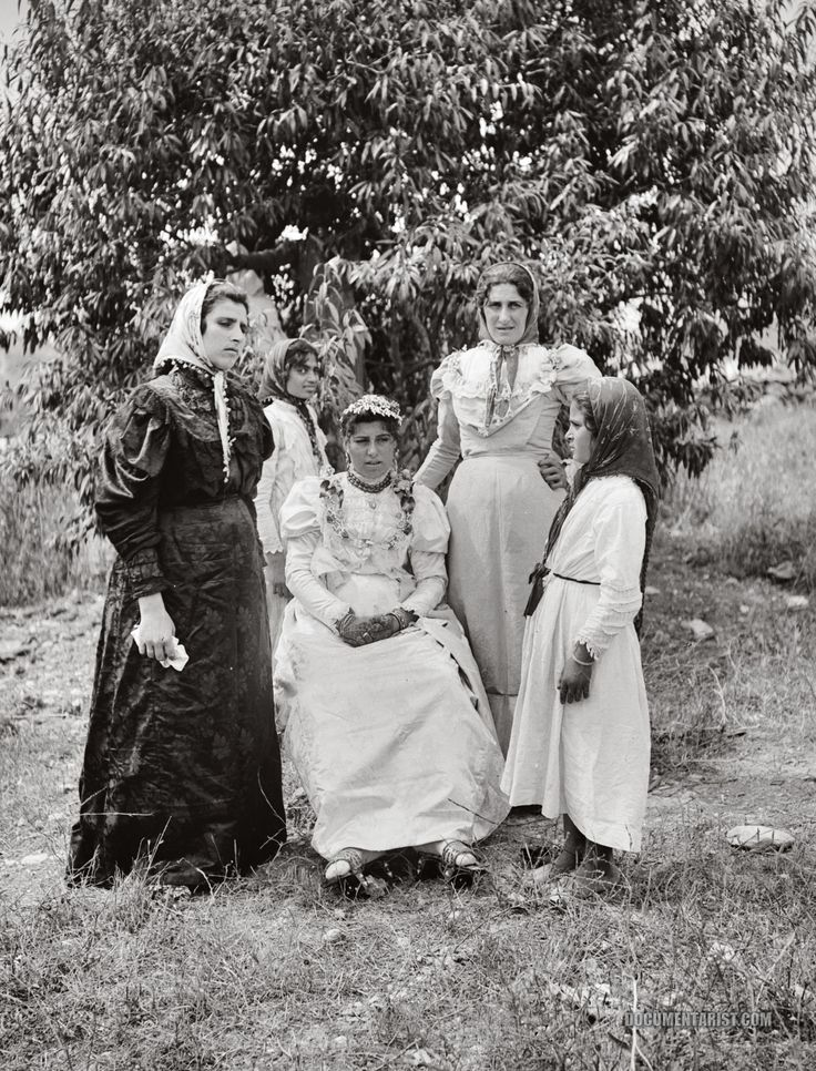 A bride of Nazareth and her family--this mix of what was at the time 'Western' modernity and the beautiful, ancient traditions of the area are striking... The bride wears a white, early Edwardian- or late Victorian-style dress paired with henna, kubkabs, and a multitude of glimmering bangles.
