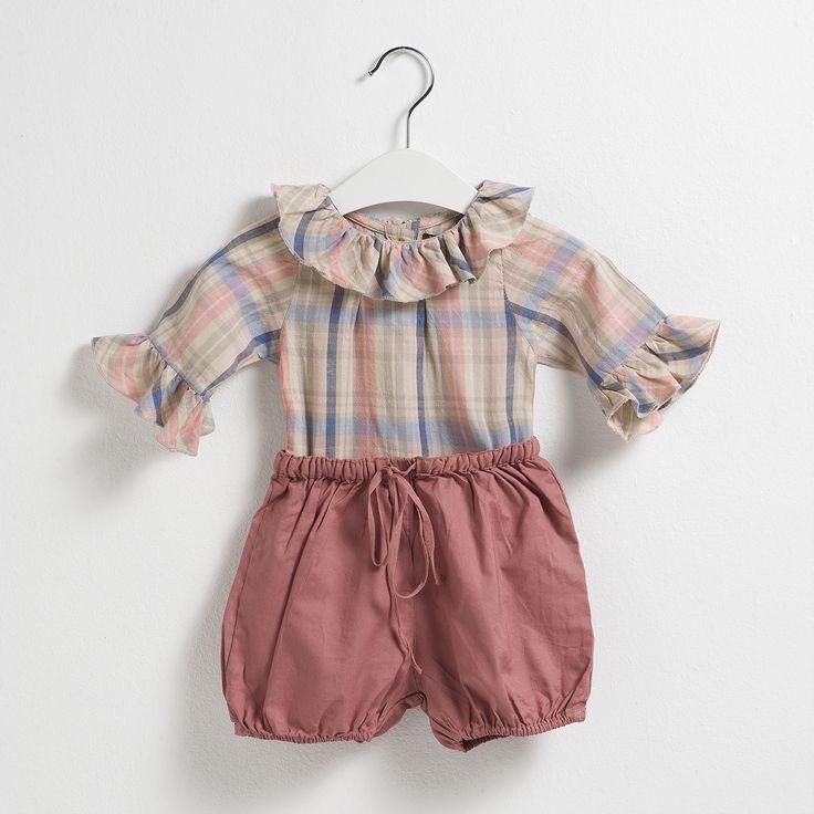 Conjunto compuesto por una camisa de cuadros rosa con maxi cuello y unas bermudas en tono teja. Moda infantil.