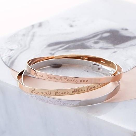 This bespoke Flat Bangle, combined with carefully chosen words, makes a trendy design, easily stackable with other bracelets!<ul> <li>Hand engraved in our stylish cursive script</li> <li>Complimentary gift box</li> </ul>Our contemporary, yet classic bangle gives the opportunity to have a longer engraving of up to 60 characters. So be creative with a special message personal to you. Whether you choose to have your bracelet etched with an inspiring quote or a meaningful memory, we guarantee…