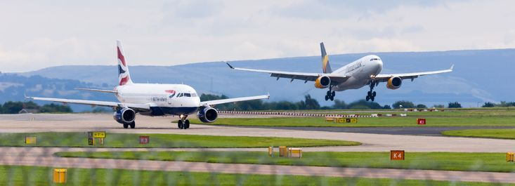 Side by side - A British Airways A320 takis as a Thomas Cook A330 lands at Manchester Airport.
