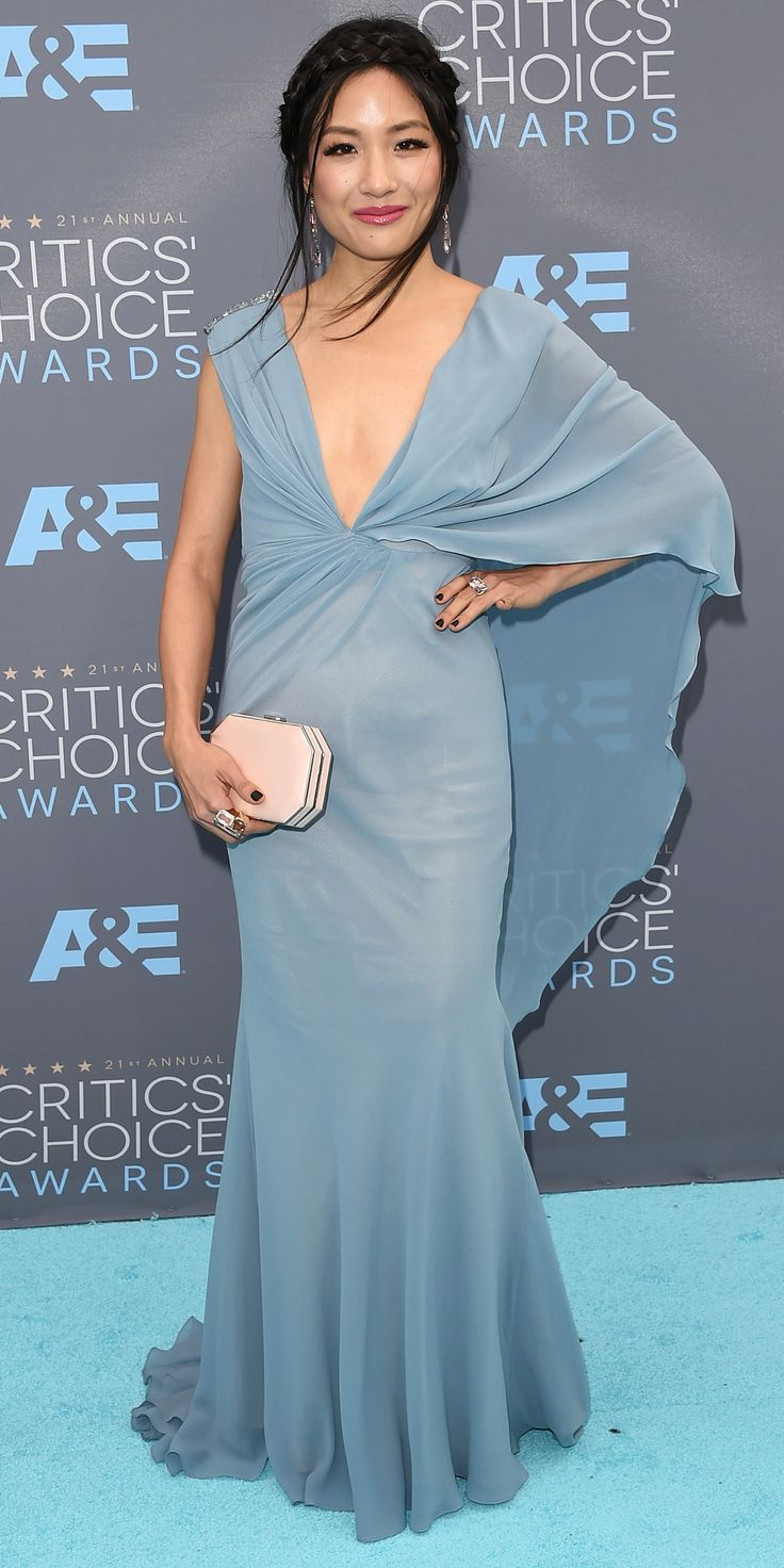 CONSTANCE WU wears a powder-blue gown with caped sleeves and a sparkling shoulder detail, plus a braided updo and blush clutch.