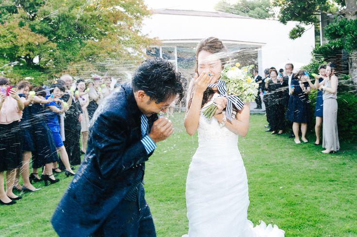 「bon voyage」がコンセプトのウェディング。結婚式が行われたのは、コンテッサリゾート。お二人の門出(出航)をお祝いするように、ゲストの皆さんがありったけの水を水鉄砲でお二人に飛ばしているところ。 photo by Takaaki Orihara / kuppography http://www.kuppography.com
