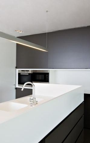 Bespoke kitchen island with a higher height side to hide the sink or accessories _