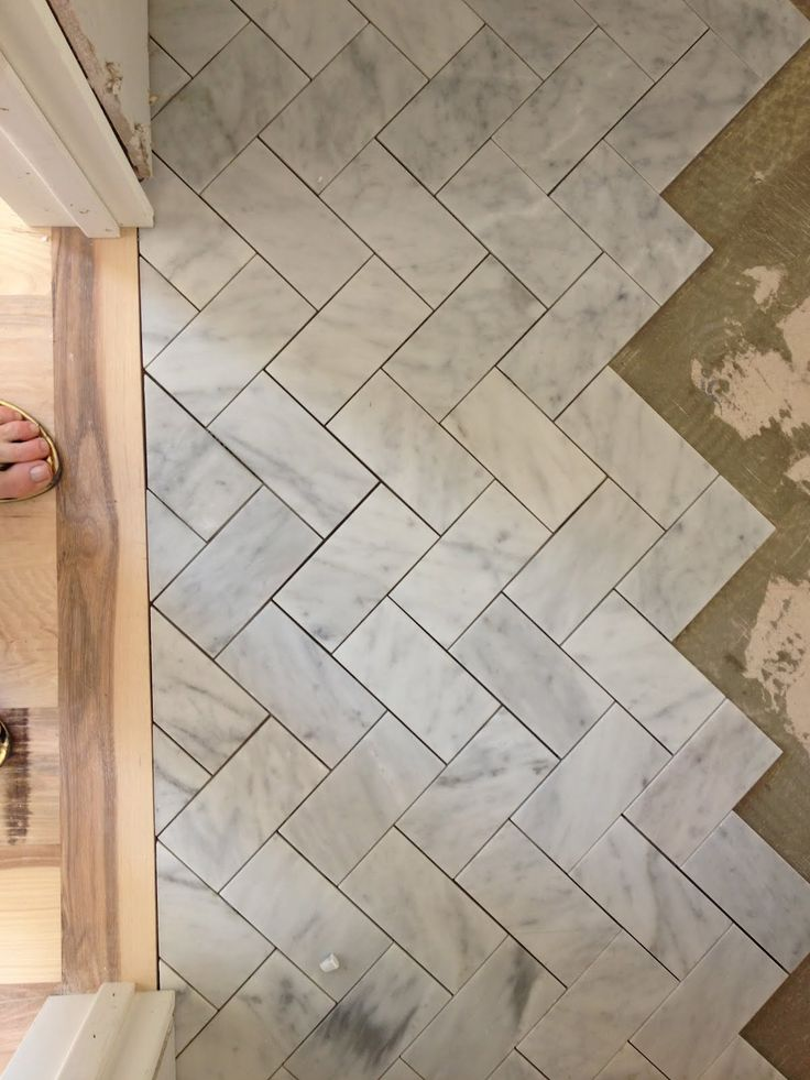 Subway tile in a herringbone pattern on the floor or backsplash.