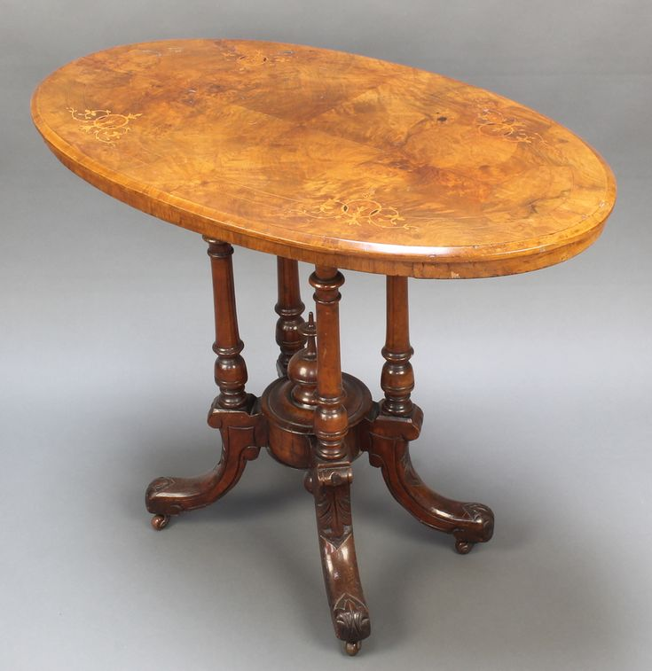 "Lot 1027,  A Victorian inlaid walnut oval occasional table raised on a quatreform base with china castors 28.5""h x 36""w x 21""d est £80-120"