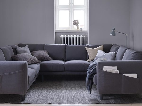 A Living Room With A Dark Grey U Shaped Sofa With Grey Legs.