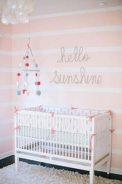 "White and pink nursery boasts walls painted in white and pink horizontal striped walls lined with ""hello sunshine"" art over a ducduc Savannah Crib dressed in pink and blue crib bedding situated under a pom pom mobile."