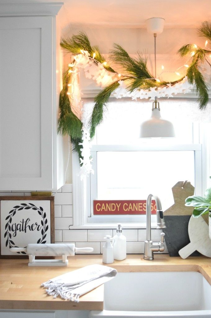 Christmas lights make everything more festive. Classic white kitchen...easy to add some Holiday to!