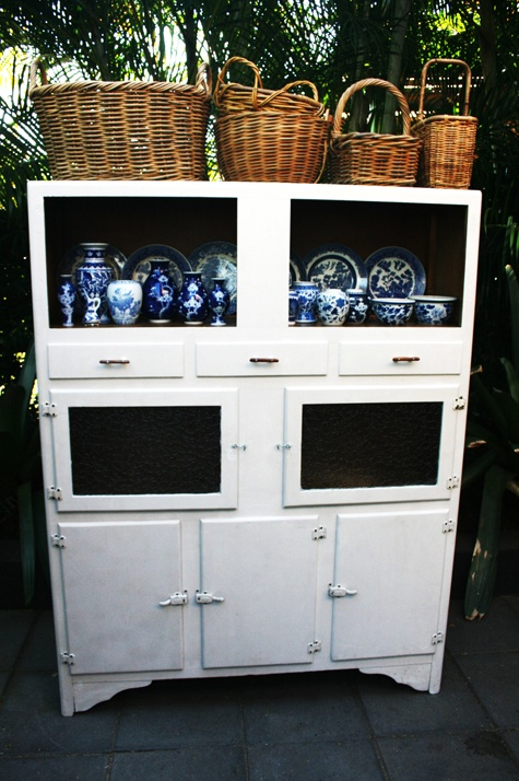 Vintage 1930s Kitchen Hutch decorated with a shelf of blue and white china porcelain and farmhouse baskets.