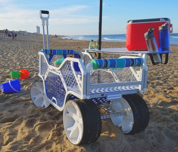 Beach cart with wide wheels to cruise over the sand, a moveable tailgate and optional table and seat back. www.sport-creations.com