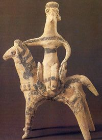 This clay model of a riding woman or goddess from Archanes Crete dated around 1100-1000 BC, Even if not related to a warrior, shows the typic riding method used by the women as well as the large and confortable saddle utilized for this kind of riding. Such figurines have been found in Attica and Crete as well as Anatolia and Near East.