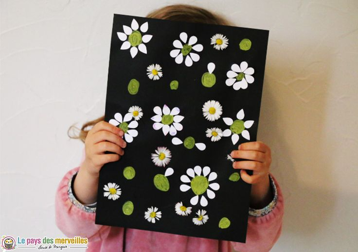 Un tableau de printemps, sur fond noir, réalisé avec des pâquerettes et des pétales découpées dans une feuille de papier blanc.