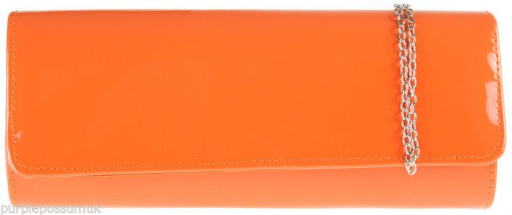 A medium large structured glossy clutch bag shoulder bag in orange The bag fastens with a flap over the top and concealed metal magnetic studs it