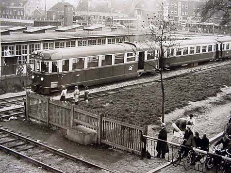 Deze prent uit het Rotterdams Gemeentearchief laat de kruising van de sporen bij 'Post-K' zien. De RTM-trein kon pas verder rijden nadat de seinen van de NS in de stand 'stop' stonden en de slagbomen weer geopend waren.