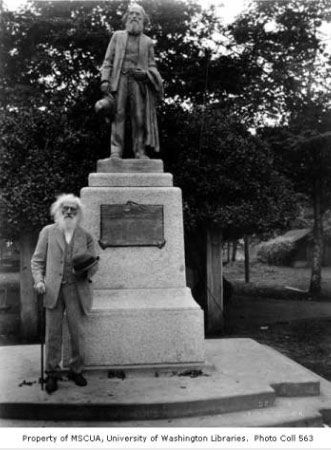 Old photo of Ezra Meeker standing by his statue in Pioneer Park Puyallup Washington