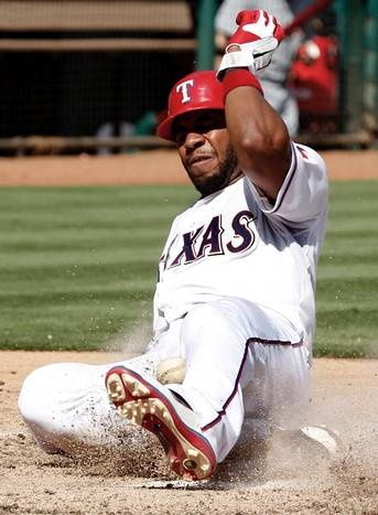 Texas Rangers' Elvis Andrus slides safely into home plate to score as he is hit by a ball tossed to Detroit Tigers relief pitcher Brayan Villarreal from catcher Alex Avila during the seventh inning of a baseball game Sunday, Aug. 12, 2012, in Arlington, Texas. Andrus scored on a wild pitch. The Rangers won 8-3.