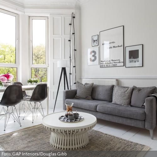 Das Wohnzimmer Ist Zu Großen Teilen In Weiß Gehalten: Tapete, Wandregal,  Couchtisch Und