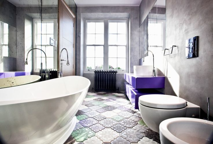 The first bathroom we visit is dominated by the bright purple vanity and multicolored, textural floor tiles. A large pedestal tub stands below a mirror at left, contrasting with the muted walls and bright colored details.